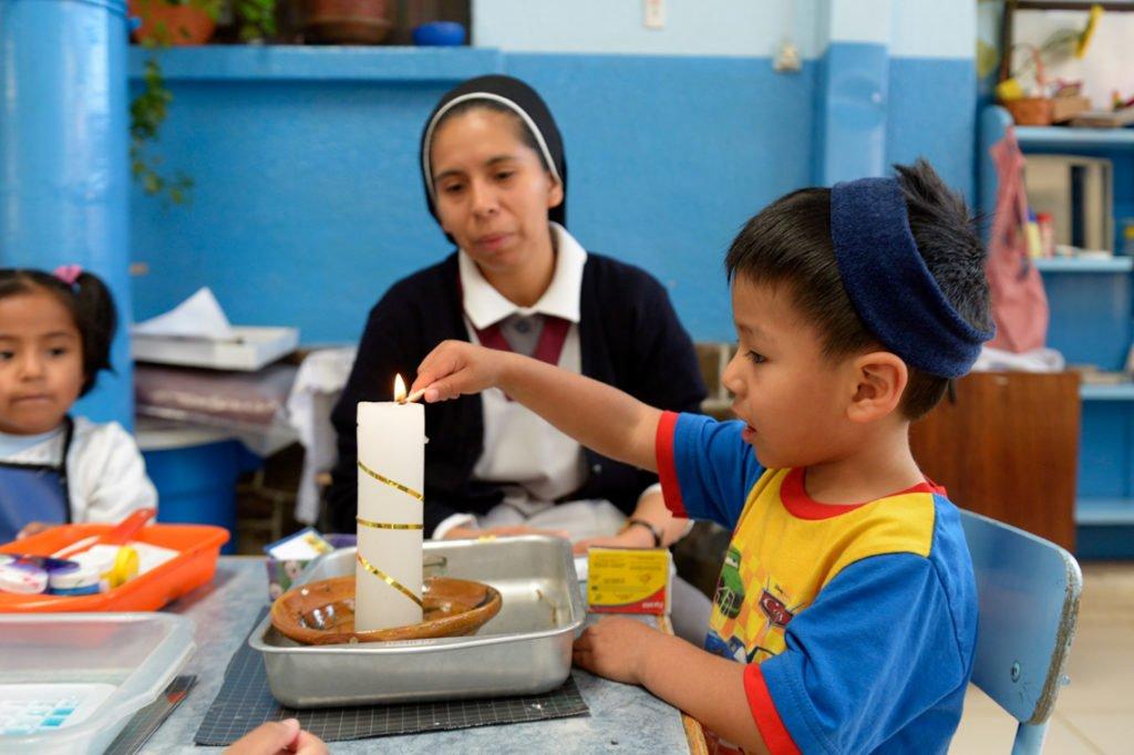 """Schwester Guadalupe unterstützt Paulo, 3 Jahre, beim Anzünden einer Kerze, Montessori-Kindergarten und -Grundschule """"Kinderhaus Santa Maria Magdalena Postel"""", Cochabamba, Departamento Cochabamba, Bolivien; Foto: Florian Kopp/SMMP"""