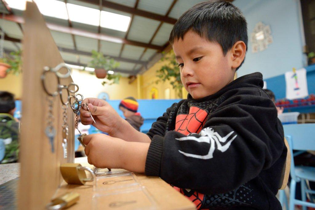 """Nicolas, 3 Jahre, arbeitet mit Vorhängeschlössern, Montessori-Kindergarten und -Grundschule """"Kinderhaus Santa Maria Magdalena Postel"""", Cochabamba, Departamento Cochabamba, Bolivien; Foto: Florian Kopp/SMMP"""