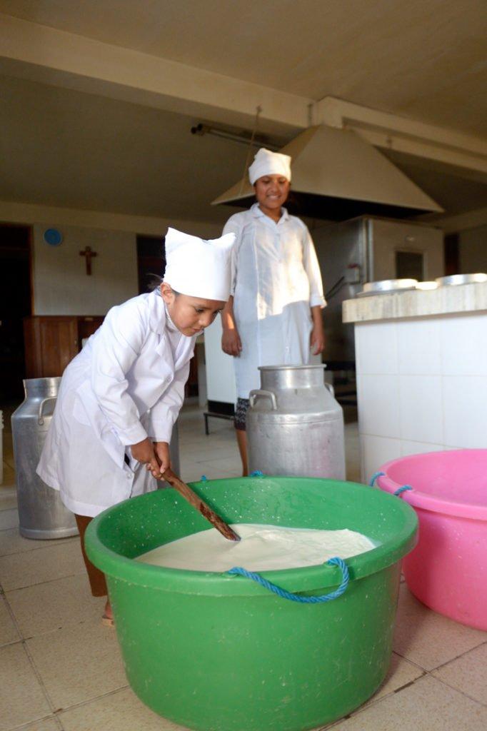 Zugeben und verrühren von Lab - Herstellung von Frischkäse, Kinderheim Comunidad La Providencia, Catro Esquinas, Departamento Cochabamba, Bolivien; Foto: Florian Kopp/SMMP