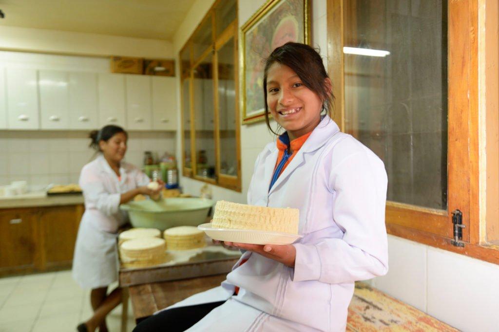 Mädchen mit einem fertigen Laib Käse - Herstellung von Frischkäse, Kinderheim Comunidad La Providencia, Cuatro Esquinas, Departamento Cochabamba, Bolivien; Foto: Florian Kopp/SMMP